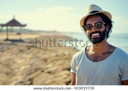 Handsome and confident. Outdoor portrait of smiling young african man on the beach.