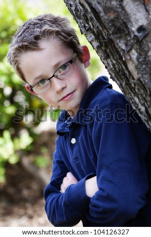 handsome and confident young boy in glasses leans against a tree with arms folded across his chest
