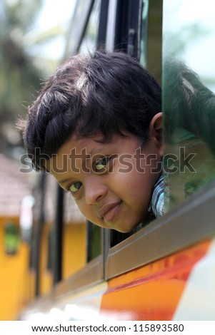 Handsome and cute little indian school kid looking back with happiness from the window of a school bus. The face shows the innocence and childishness of the 6 year old boy with a smile on his face