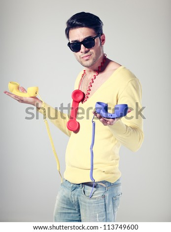 handsome and funny guy with hipster glasses and retro colorful phones