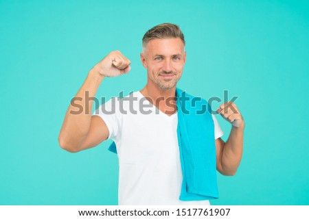 Handsome and muscular. Handsome man with towel on blue background. Athlete flex biceps triceps arm. Male adult with unshaven handsome face and stylish blond hair. Handsome and attractive.