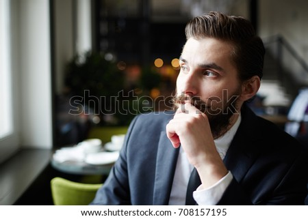 Handsome and neat young businessman contemplating in cafe