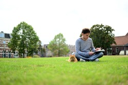 Handsome and relaxed young man reading a book while sitting in a park with his lovely cat.