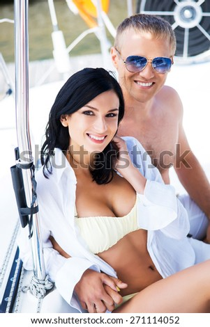 aed4ad2aac Handsome and rich man and a beautiful and sexy woman in swimsuit relaxing  on a sailing