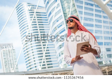 Handsome arab business man hold the digital tablet and looking to left side. Arab business man standing outside office. Finishing up a meeting, Connection concept. with copy space #1135367456