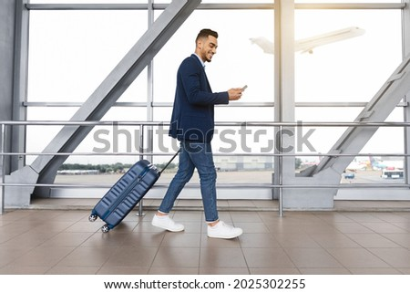 Handsome arab guy using smartphone while walking with suitcase at airport terminal, young middle eastern man browsing mobile internet on cellphone while going to flight boarding, side view