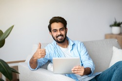 Handsome Arab Man With Digital Tablet Sitting On Couch At Home And Showing Thumb Up At Camera, Positive Eastern Guy Recommending New Application While Relaxing On Sofa In Living Room, Free Space