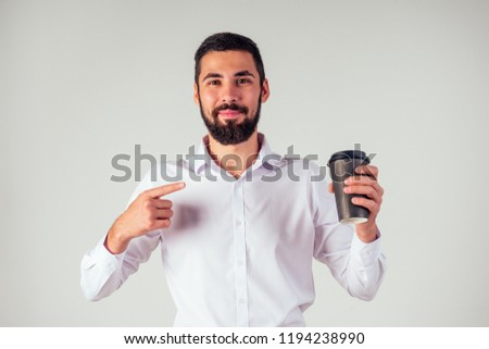handsome Arab Sheikh businessman black beard in a white shirt and black trousers holding a plastic paper cup and drinking coffee on white background studio shot