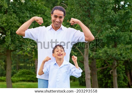 Handsome arabian man and his son showing muscles