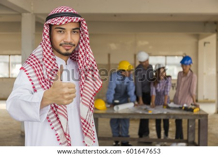 Handsome Arabic business man with thumb up, on front Team Business people,Engineer with partner reviewing and discussing construction plans to success,construction project concept