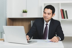 Handsome Asian businessman using laptop computer in the office - soft tone, selective focus