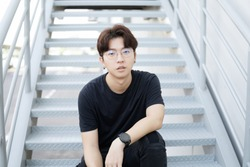 Handsome asian CASUAL glasses man sit on a staircase and smile posing on gray background. Portrait of young KOREAN against staircase background.
