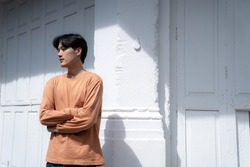 Handsome asian guy wearing long sleeve t-shirt orange color standing in front of white door background with copy space