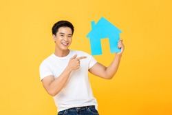 Handsome Asian man holding and pointing to house cutout isolated on yellow studio background