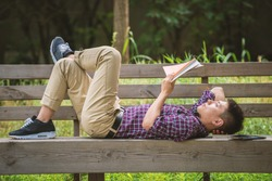 Handsome Asian man is reading a book lying on bench with one leg crossing on his knee
