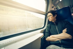 Handsome asian man looking through train window, warm light tone, with copy space