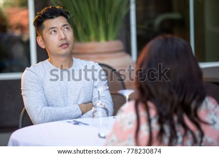 Handsome asian man on an outdoor date with a black female.  The couple are sitting in a restaurant or cafe setup for speed dating.  He looks bored and disappointed. #778230874
