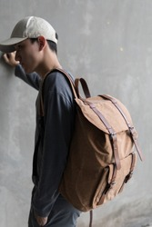 Handsome Asian man with lightbrown ( cork ) canvas backpack smiling standing with cap.