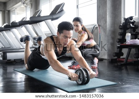 Handsome asian workout by ab wheel on yoga mat exercise with woman are trainers at gym. Concept of exercise in gym.