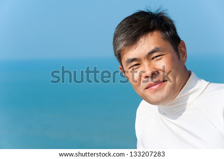 handsome asian young man looks into camera smiling, blue sea and sky