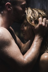 Handsome athletic man kissing and embracing beautiful woman in the shower