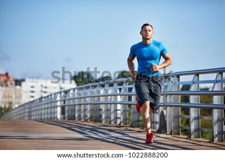 Handsome athletic man out jogging in the city
