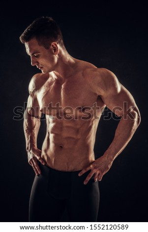 Handsome athletic man showing his trained body on dark background #1552120589