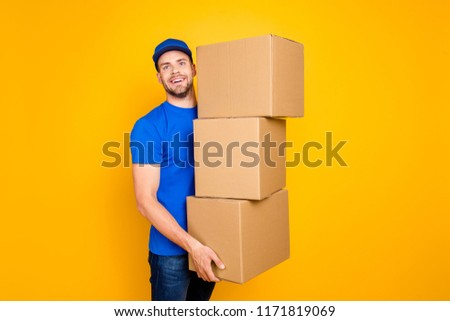 Handsome attractive cheerful bearded deliver in blue uniform and jeans with stubble, holding three big boxes in arms, isolated over bright vivid yellow background