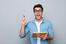 Handsome, attractive, glad, positive, funny guy in glasses with wide open mouth finally found a solution how to make exercise, having raised pen and notebook in hands, isolated on grey background