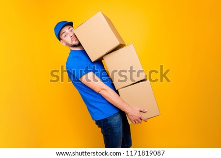 Handsome attractive tired bearded deliver on-time guy in blue uniform and jeans with stubble, bristle holding three large hard big boxes in arms, isolated over bright vivid yellow background