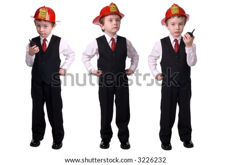 handsome attractive young boy dressed as a fire chief- in suit with helmet and walkie-talkie and hand on hip on white background.