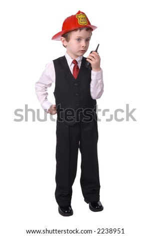 handsome attractive young boy dressed as a fire chief- in suit with helmit and walkie-talkie and hand on hip on white background.
