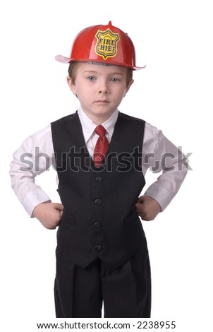 handsome attractive young boy dressed as a fire chief- in suit with helmit on white background.