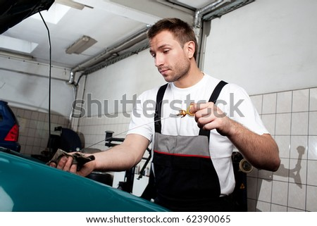 Handsome auto mechanic checking engine oil in car service.
