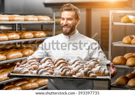 Handsome baker in uniform holding tray full of freshly baked croissants at the manufacturing ストックフォト ©