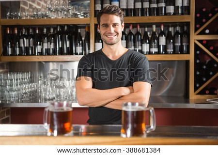 Handsome bar tender standing behind his counter in a pub