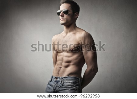 Handsome bare-chested man wearing fashion sunglasses