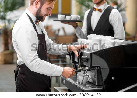 Handsome barista in uniform making coffee standing with waiter in classical renaissance cafe patio