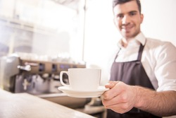 Handsome barista offering a cup of coffee to you at the coffee shop. Blurred background.