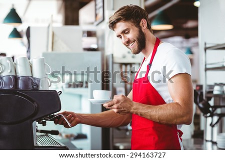 Handsome barista preparing a cup of coffee with the coffee machine