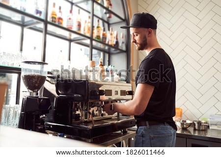 Handsome barista with beard making cappuccino on coffee machine Foto d'archivio ©