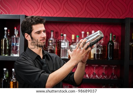 Handsome barman professional at posh bar making cocktail drinks