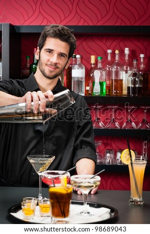 Handsome barman professional at posh bar making cocktail drinks - stock photo