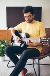 Handsome beard man is taking online guitar course. Guy in a yellow t-shirt is playing acoustic guitar at home with beautiful interior. Doing classes of chords while staying on quarantine