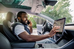 Handsome bearded African man touches the touchscreen in his new high-tech electric vehicle while while talking by phone and smiling. Self driving vehicle concept