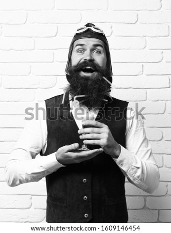 handsome bearded aviator man with long beard and mustache on happy face holding glass of alcoholic shot in vintage suede leather waistcoat with hat, and glasses on white brick wall background