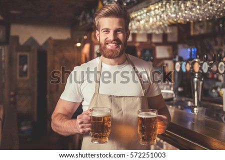 Handsome bearded bartender in apron is holding beer, looking at camera and smiling while standing near the bar counter in pub