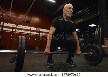 Handsome bearded Caucasian male pensioner with strong muscled arms holding barbell, ready to do deadlift. Self determined elderly man in sportswear working on stamina and building muscles in gym