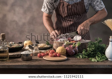 Handsome bearded cheef cook prepairing spaghetti on a kitchen, Chef cooks meal #1121942111