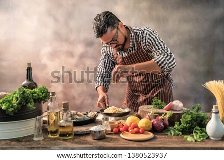 Handsome bearded cheef cook prepairing spaghetti on a kitchen, Chef cooks meal #1380523937
